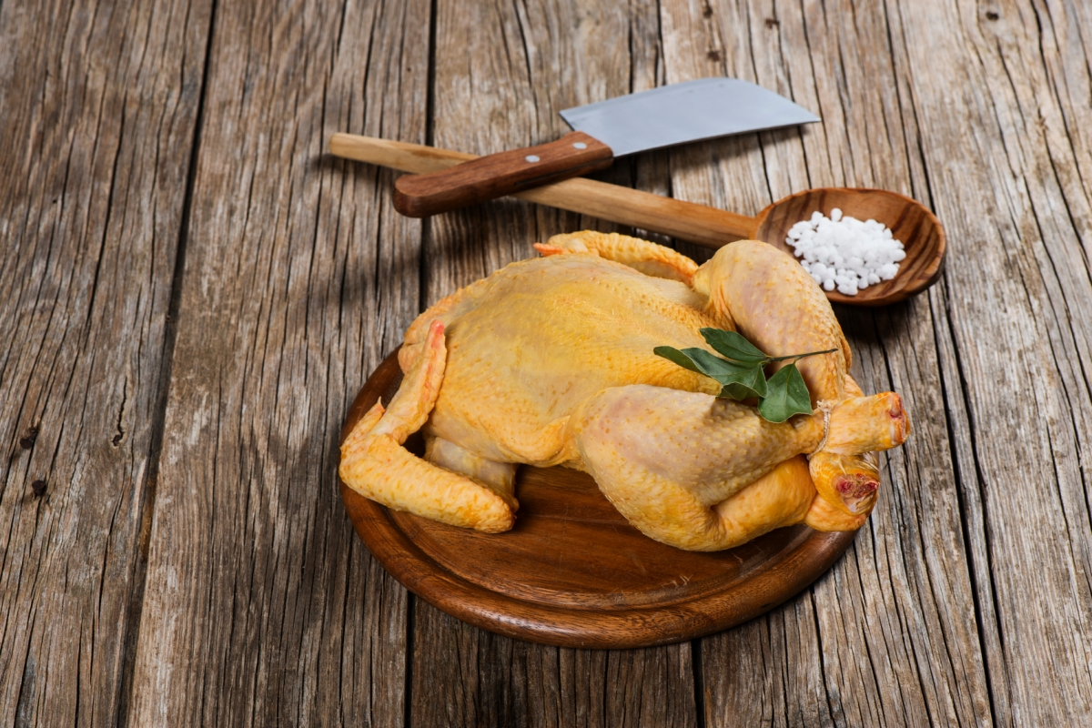 Whole raw chicken on a old wooden  background with copy-space