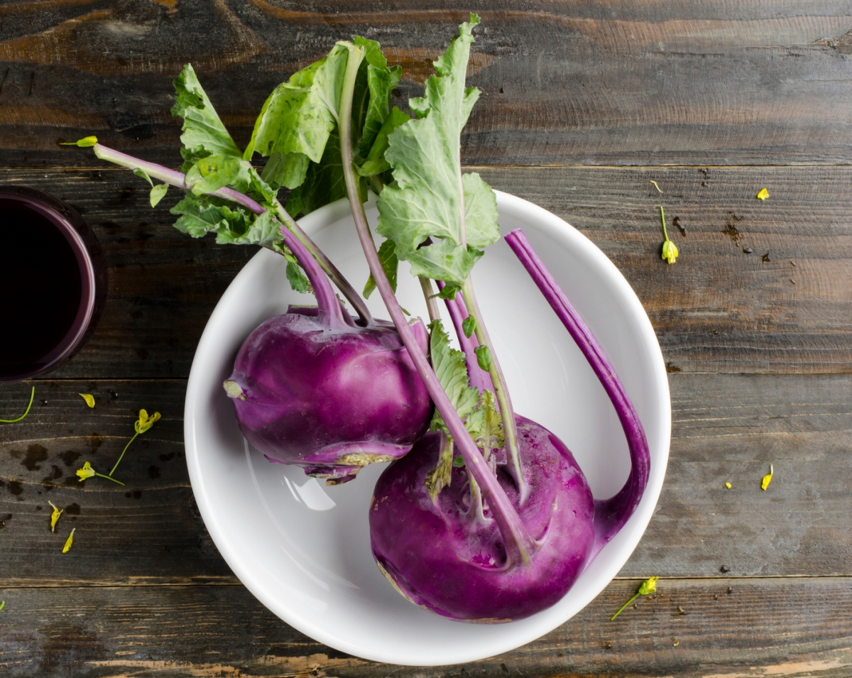 Purple kohlrabi in the bowl on wooden background
