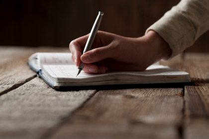 hand writes with a pen in a notebook